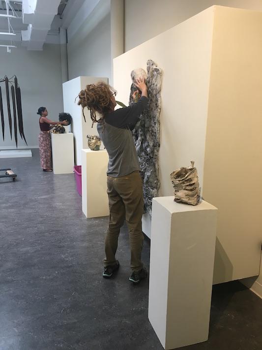 An intern hanging an art piece on the Weems Gallery wall.