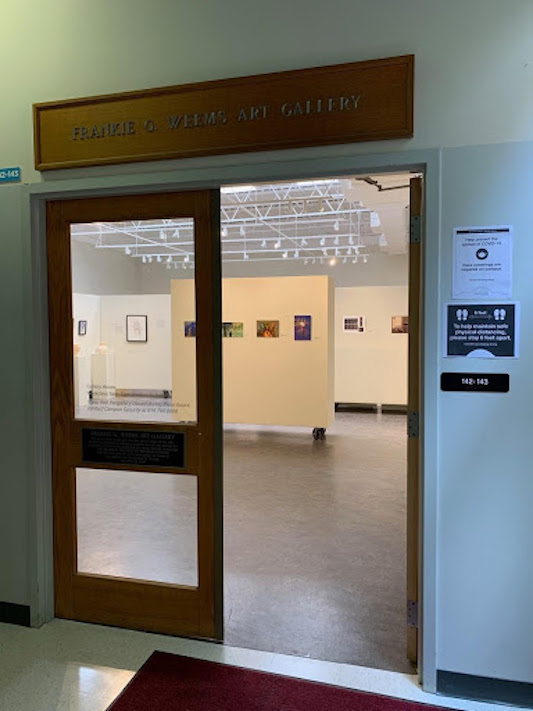 Two doors allowing entrance into a gallery with lots of lights.