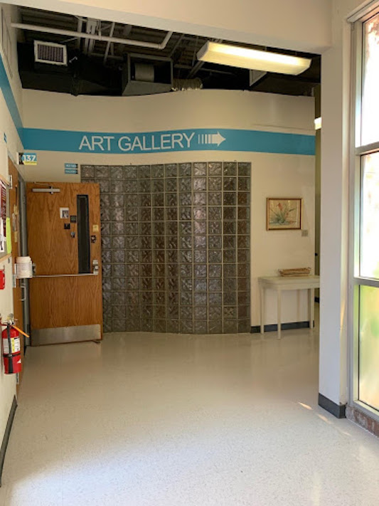 """Hallway in Weems gallery with a blue strip on wall that reads """"Art Gallery"""" and has an arrow pointing right."""