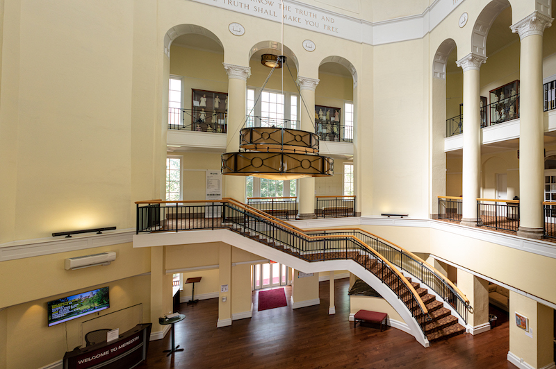 Interior of Johnson Hall with a chandelier and staircase.