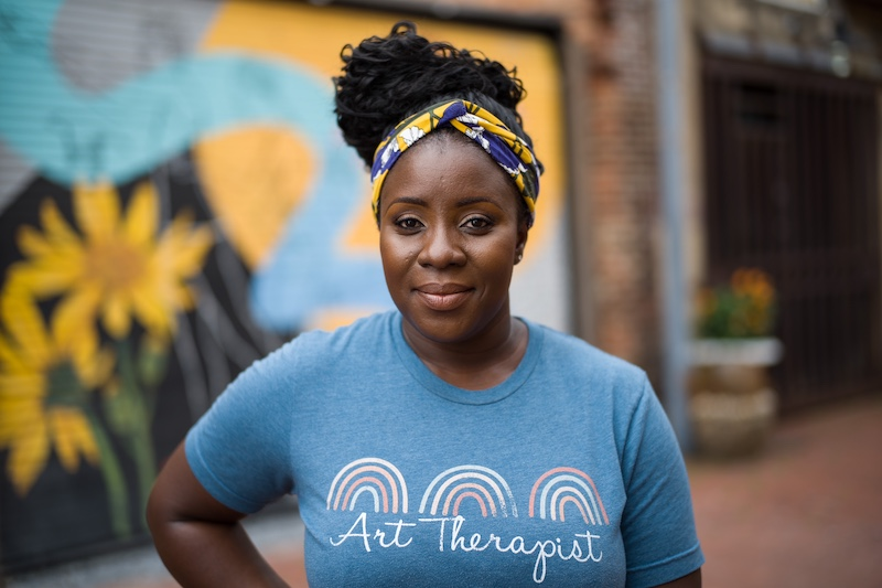 """Woman smiling with a t-shirt that says """"art therapist"""" and a colorful mural behind her."""